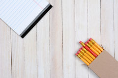 Pencils and Paper on Wood Surface Stock Photo