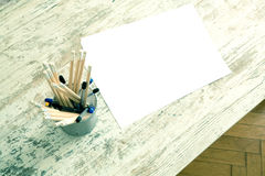 Pencils and paper on a wooden Desktop. Some Pencils and a blank sheet of paper on a wooden Desktop Royalty Free Stock Photo