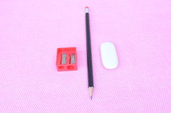 Pencils, pens, eraser and pencil sharpener located on the notepads Stock Photography