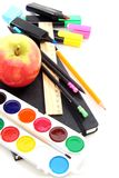 Pencils, pens and a notebook with an apple. Royalty Free Stock Photo