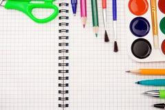 Pencils, pens, paint brush and scissors on paper Stock Photo