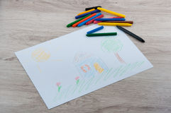 Pencils and picture of house on wooden table Royalty Free Stock Photos
