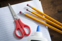 Pencils, Scissors and a Bottle of Glue on Notebook Paper stock photos