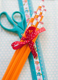 Pencils, scissors, and ruler. A pencil bouquet tied up with a red polka dot bow sits on top of a blue scissors and a child's ruler on a polka dot background Royalty Free Stock Photo
