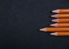 Pencils set on a blackboard Stock Images