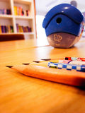 Pencils and a sharpener on table Royalty Free Stock Image