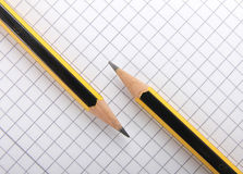 Pencils on sheet of squared Royalty Free Stock Image