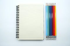 Pencils in various colors and linear notebook Royalty Free Stock Image