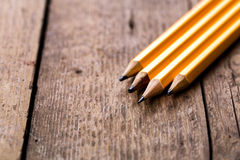 Pencils on wood background. Four simple yellow pencil on wooden background Royalty Free Stock Images