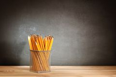 Pencils on a wooden school desk in front of a black chalkboard school. Education concept - the desk in the auditorium.  stock photo