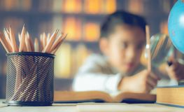 Pencils on a wooden table and asian child industrious is sitting at a desk . background. Educational background royalty free stock photography