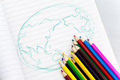 Pencils and world map. Colorful pencils and world map on the notebook Stock Images