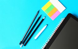 Pencils, writing paper and tablett on a blue background and back to school concept royalty free stock photo