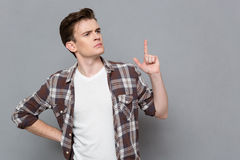 Pencive young man having an idea and pointing up Royalty Free Stock Photos