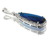 Pendant with blue gem on white. Background Royalty Free Stock Image