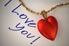 Pendant brillant rouge de coeur, avec une chaîne d'or, sur le livre blanc et le t Photo libre de droits