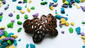 Pendant butterfly from coconut on a background of multi-colored stones.  Royalty Free Stock Photos