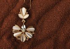 Pendant d'or de bijoux avec la nacre et diamants sur le backgrou brun Images libres de droits