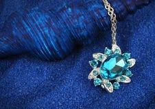 Pendant de bijoux avec des gemmes sur le fond bleu-foncé de sable Photo stock