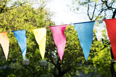 Pendant decoration background of trees. Garland decoration at the fair. Decorations of colorful pennants and colorful flag in the courtyard of the festival Royalty Free Stock Photography