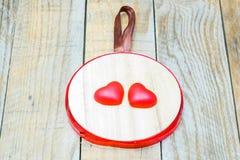 Pendant en bois avec deux coeurs rouges Photographie stock libre de droits