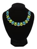 Pendant with green and blue gem stones on black mannequin Royalty Free Stock Image