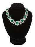 Pendant with green gem stones on black mannequin Royalty Free Stock Image