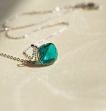 Pendant with green stone. A beautiful pendant with a green stone on a thin chain, illuminated by the sun. Transparent faces of stone are the sun Royalty Free Stock Photos