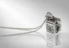 Pendant on grey background. Silver pendant wiht chain on grey background Royalty Free Stock Photo