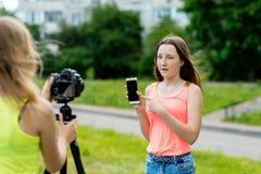 Pendant l'été dans la ville sur la rue Fille de deux amies Écrit la vidéo à l'appareil-photo Le concept de jeunes bloggers Image libre de droits