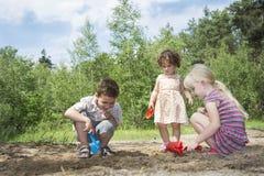 Pendant l'été dans les bois creusant le petit au sol de jeu d'enfants Photo libre de droits