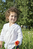 Pendant l'été, la fille bouclée se tenant dans l'herbe grande, et l'herbe Photographie stock libre de droits