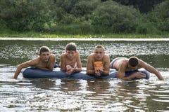 Pendant l'été sur la rivière sur le matelas gonflable sont le swimmi Image stock