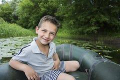 Pendant l'été sur la rivière un petit garçon s'asseyant dans un canot en caoutchouc Photo stock