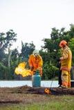 Pendant la lutte contre l'incendie s'exerçante, les réservoirs à gaz avec le feu, le sapeur-pompier avec le feu et le costume pou photographie stock libre de droits
