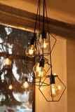 Pendant lamps with glowing light bulbs near window. Indoors stock photos