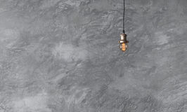 Pendant lamps in loft style against rough wall with gray cement. Plaster. Edison light bulbs Stock Images