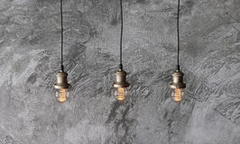 Pendant lamps in loft style. Loft pendant lamps on the background of rough cement plaster on the wall. Minimal loft interior. Edison light bulbs Stock Photos