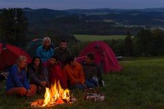 Feu de camp de observation campant de personnes ensemble près des tentes Photographie stock