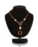 Pendant with an orange gem on mannequin Royalty Free Stock Photos