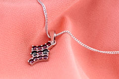 Pendant with precious stones on a chain. Royalty Free Stock Image