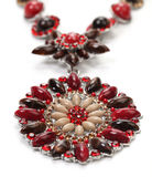 Pendant of red gems with necklace. Closeup photo of pendant with necklace over white Stock Image