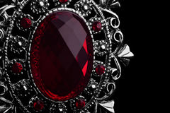 Pendant with red gemstone. Macro image of pendant with red gemstone on black background Stock Image