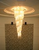 Pendant style chandelier. House interior with a sparkling chandelier in a hanging pendant style and a textured wall-hanging behind in a Chinese home Stock Photography