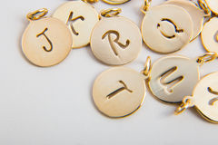 Pendants. Circular cut of gold with letters  in the middle Royalty Free Stock Image