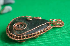 Pendent from the stone braided by a copper wire Stock Photo
