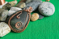 Pendent from the stone braided by a copper wire Royalty Free Stock Photos