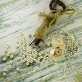 Pendente in conchiglia e vecchia chiave fra le perle sparse Fotografia Stock Libera da Diritti