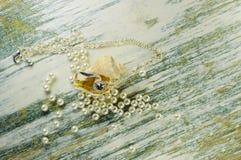 Pendente in conchiglia fra le perle sparse Fotografia Stock Libera da Diritti