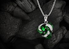 Pendente dei gioielli con lo smeraldo della gemma sul fondo scuro del carbone, copys Immagine Stock